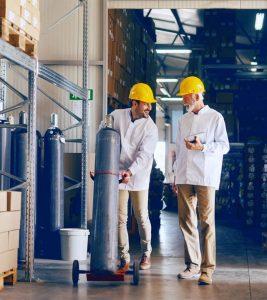 Двама работници с жълти каски превозват опасни товари в склад